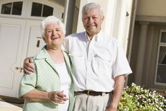 Senior couple standing outside their home Stock Photos