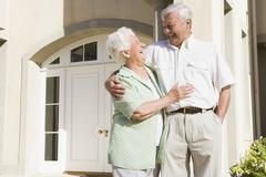 Senior couple standing outside their home - stock photo