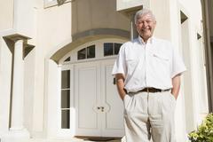 Senior man standing outside his home - stock photo