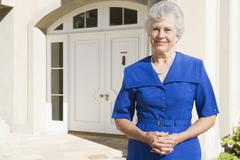 Senior woman standing outside her home Stock Photos