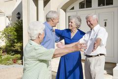 Two senior couples greeting each other with open arms Stock Photos