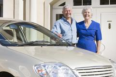 Senior couple standing with their car outside their home Stock Photos