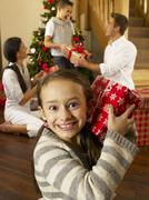 Hispanic family exchanging gifts at christmas Stock Photos