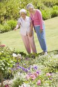 Two senior women in a flower garden - stock photo
