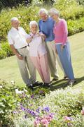 Two senior couples in a flower garden - stock photo