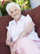 Senior woman sitting outdoors on a chair Stock Photos