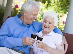 Senior couple sitting outdoors having a glass of red wine - stock photo