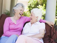 Two senior women sitting outdoors on a chair - stock photo