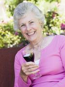 Senior woman sitting outdoors on a chair with a glass of red wine Stock Photos