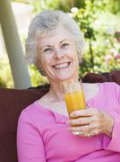 Senior woman sitting outdoors with a glass of orange juice - stock photo