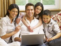 Hispanic family shopping online Stock Photos