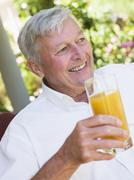 Senior man sitting outdoors with a glass of orange juice Stock Photos
