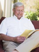 Senior woman sitting outdoors on a chair reading a book - stock photo