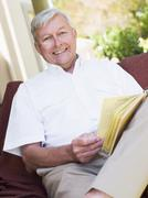 Senior woman sitting outdoors on a chair reading a book Stock Photos
