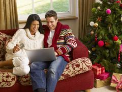 Young hispanic couple christmas shopping online Stock Photos