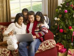 Hispanic family christmas shopping online Stock Photos