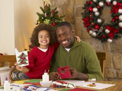african american father and mixed race son making christmas cards - stock photo
