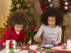 Mixed race children making christmas cards Stock Photos