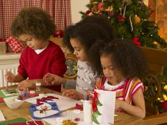 mixed race children making christmas cards - stock photo