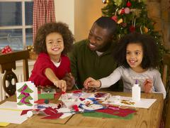 african american father making christmas cards with children - stock photo