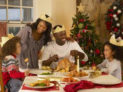 Mixed race family having christmas dinner Stock Photos