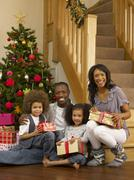 young african american family with christmas tree and gifts - stock photo