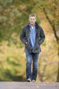 Man walking through autumn park listening to mp3 player Stock Photos