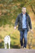 man walking dog through autumn park listening to mp3 player - stock photo