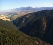 Aerial shot of forest and mountainside city in distance Stock Footage
