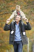 Man with young son on shoulders autumn park Stock Photos