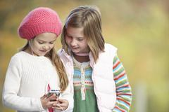 two young girl outdoors with mp3 player - stock photo