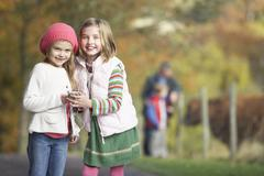 Two young girl listening to mp3 player outdoors Stock Photos