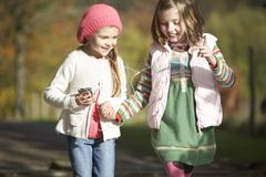 two young girl listening to mp3 player outdoors - stock photo