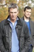 Two men standing outside in autumn woodland Stock Photos