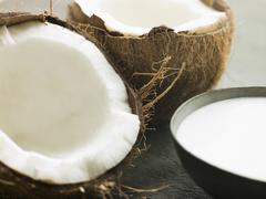 Dish of Coconut Milk with a Split Fresh Coconut Stock Photos