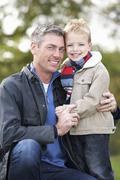 father and son hugging on outdoor autumn walk - stock photo
