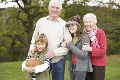 grandparents with grandchildren holding football outside - stock photo