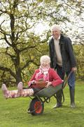 Senior couple man giving woman ride in wheelbarrow Stock Photos