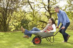 couple with man giving woman ride in wheelbarrow - stock photo