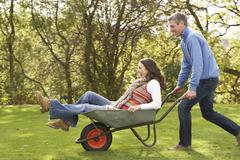 Couple with man giving woman ride in wheelbarrow Stock Photos
