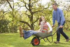 Stock Photo of couple with man giving woman ride in wheelbarrow