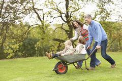 Stock Photo of parents giving children ride in wheelbarrow