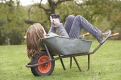 young girl laying wheelbarrow using smart mobile phone - stock photo