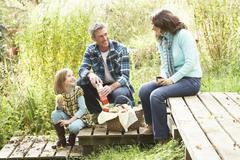 Parents and children having picnic in countryside Stock Photos