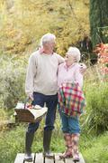 senior couple outdoors with picnic basket by autumn woodland - stock photo