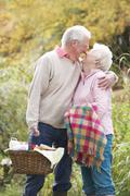 romantic senior couple outdoors with picnic basket by autumn woodland - stock photo