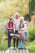 grandparents with grandchildren carrying picnic basket by autumn woodland - stock photo