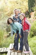 Family group standing outdoors on wooden walkway in autumn landscape Stock Photos