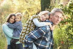 Perheyhteisön ulkona syksyllä maisema vanhemmat antavat chiildren possu Kuvituskuvat