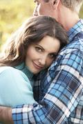 close up of romantic couple embracing by autumn woodland - stock photo